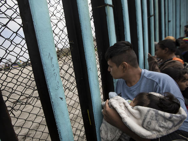 Central American migrants look through the border wall near the ocean in Tijuana, Mexico, in April.