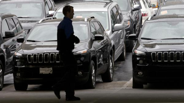 A worker on a Chrysler car lot passes lines of Jeeps in 2014. The House on Tuesday passed a measure to roll back guidance on auto lending issued by the Consumer Financial Protection Bureau.