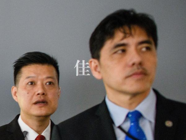 "This 2017 photo shows the man on the right, identified by local Hong Kong media as former CIA agent Jerry Chun Shing Lee, standing in front of a member of security at the unveiling of Leonardo da Vinci's ""Salvator Mundi"" painting at the Christie's showroom in Hong Kong."