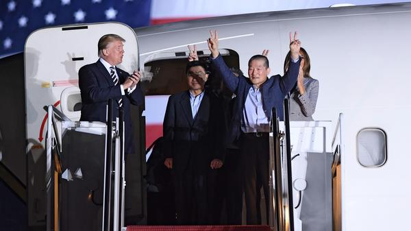 President Trump applauds as Kim Dong Chul (2nd R) gestures upon his return with Kim Hak Song (C) and Tony Kim (behind) after they were freed by North Korea, at Joint Base Andrews in Maryland.