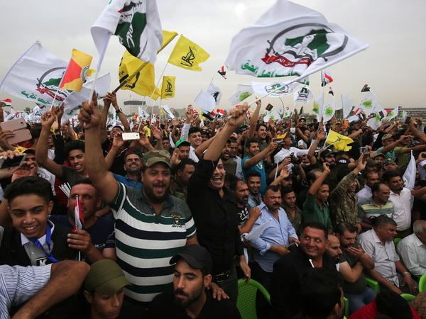 Iraqis wave flags at a campaign rally for the Fateh Alliance, a coalition that includes Iranian-supported paramilitaries, in Baghdad on May 7.