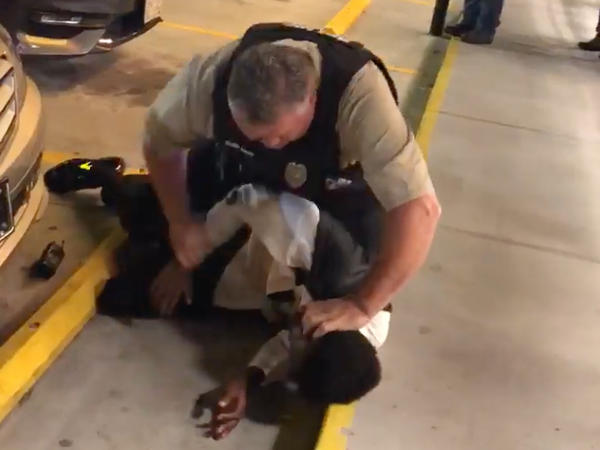 The video shows a white police officer choking a young tuxedo-clad man who is African-American, pushing him against a storefront and then slamming him to the ground outside a North Carolina Waffle House.
