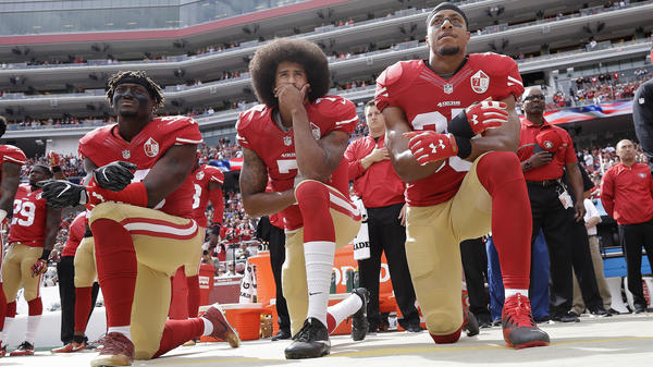 San Francisco 49ers linebacker Eli Harold (left), quarterback Colin Kaepernick and safety Eric Reid kneel during the national anthem before an NFL football game against the Dallas Cowboys in 2016.