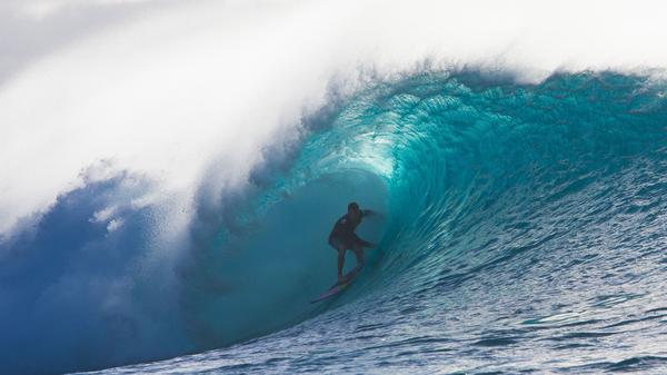 """A surfer rides the barrel of a wave during a late afternoon on the North shore of Oahu, Hawaii. Could a different kind of """"blue wave"""" come with the 2018 midterms?"""