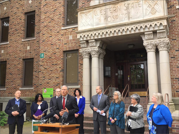 Washington Gov. Jay Inslee, flanked by lawmakers and state officials, announces a plan to move all psychiatric patients who have not committed crimes out of the state hospitals by 2023.