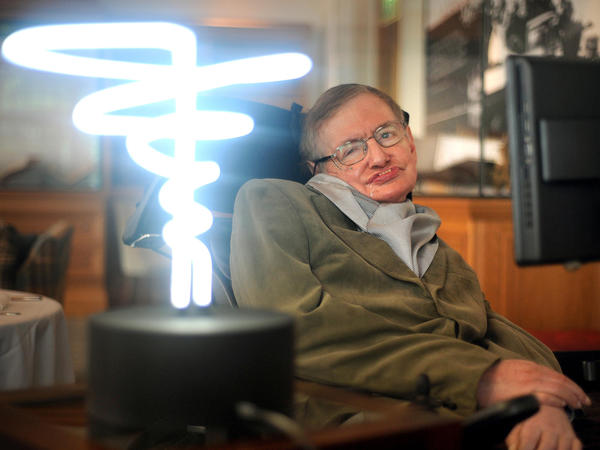 In this Feb. 25, 2012 photo, Professor Stephen Hawking poses beside a lamp titled 'black hole light' presented to him during his visit to the Science Museum in London. A service will be held for him in the same city this June. Hawking, whose brilliant mind ranged across time and space though his body was paralyzed by disease, died in March 2018.