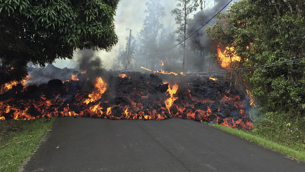 A lava flow on May 6 moves across Makamae Street in the Leilani Estates subdivision near Pahoa on the island of Hawaii. Kilauea volcano has destroyed more than two dozen homes since it began spewing lava hundreds of feet into the air last week.