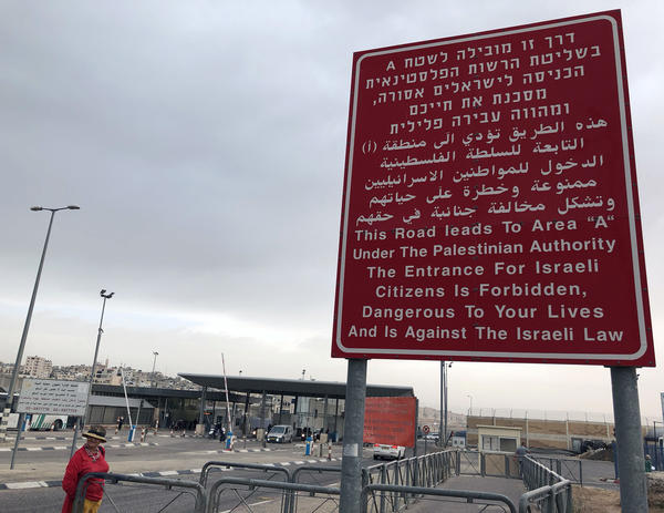 A sign at an Israeli checkpoint warns Israelis not to enter. A Palestinian neighborhood is located behind the checkpoint.