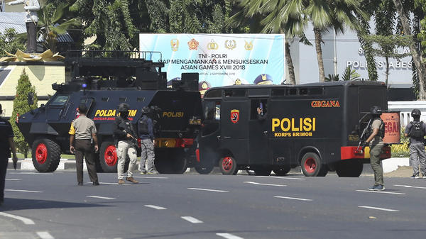 Response vehicles are parked outside local police headquarters following an attack in Surabaya Monday. The headquarters in Indonesia's second largest city was attacked by suspected militants who detonated explosives from a motorcycle, a day after suicide bombings at three churches in the city by members of one family killed a number of people.