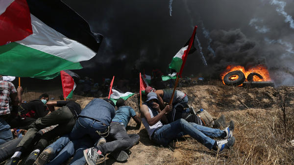 Palestinian demonstrators take cover from Israeli fire and tear gas during a protest against the U.S. move of its embassy to Jerusalem, at the Israel-Gaza border in the southern Gaza Strip.