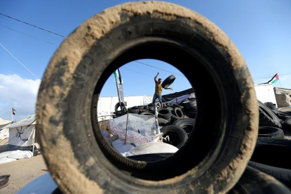 A man carries tires to be burned as Palestinians prepare to demonstrate along the border with the Gaza Strip.