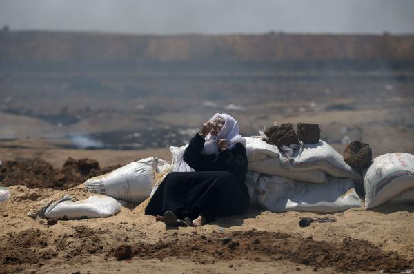 A Palestinian woman sniffs a fragrance to counter the effect of tear gas during clashes with Israeli security forces near the border between Israel and the Gaza Strip.