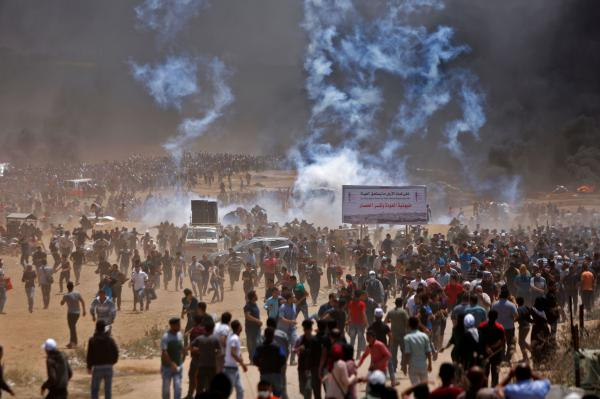 Palestinians run from tear gas during clashes with Israeli security forces.