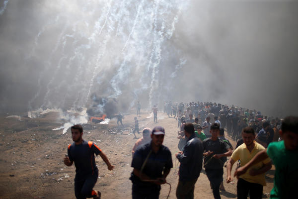 Palestinian demonstrators run from tear gas fired by Israeli troops during a protest against the U.S. Embassy move to Jerusalem.