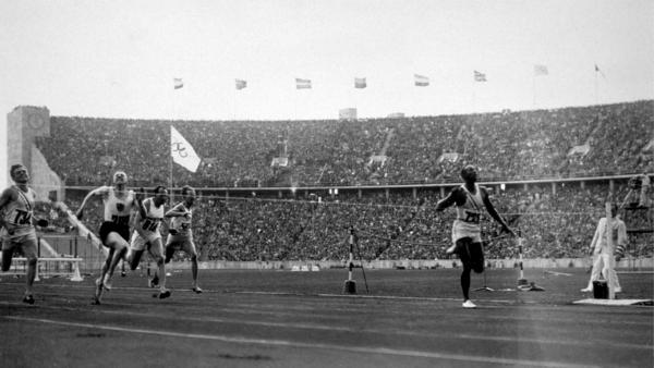 Jesse Owens crosses the line to win the 100-meter dash, one of four gold medals he won at the 1936 Olympics in Nazi Germany. The new book <em>Upon Further Review </em>imagines 31 counterfactual scenarios in sport, including the possibility of the United States boycotting the 1936 games.