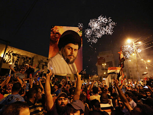 Supporters of Shiite cleric Muqtada al-Sadr carry his image as they celebrate in Tahrir Square, Baghdad, Iraq, Monday, after the political alliance he backs appeared to gain the most votes in parliamentary elections.