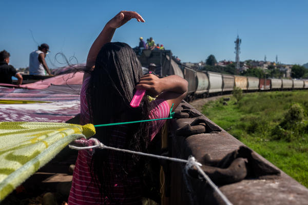 Andrea, 14, brushes her hair. A man living across the railroad tracks offered up his house for people in the caravan to shower or wash their hair while the train stopped briefly. Mazatlán, Oct. 23, 2017.