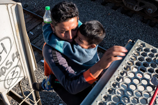 José gets off <em>La Bestia</em> with his son Andrée while the train stops on its way to Tijuana, Mexico, Oct. 22, 2017.