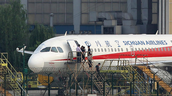Employees check a Sichuan Airlines Airbus A-319 on Monday after an emergency landing in Chengdu in China's northwestern Sichuan province. A cockpit window that broke midflight has been covered up; the flight's co-pilot was partially sucked out of the window.