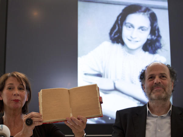 Teresien da Silva and Ronald Leopold of the Anne Frank Foundation show a facsimile of Anne Frank's diary at a news conference in Amsterdam on Tuesday. Researchers used digital photo editing techniques to uncover text on two pages of the diary, revealing risqué jokes and an explanation of sex and prostitution.