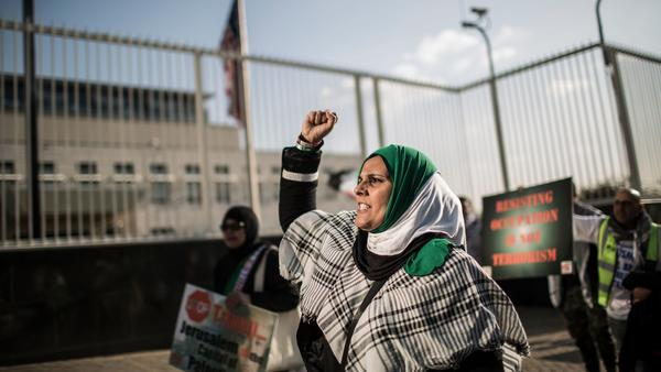 A pro-Palestinian protester raises her fist at a rally outside the U.S. Consulate General in Johannesburg on Tuesday. The South African demonstrators were just some of those who took to city streets to protest the killing of dozens of people along the Gaza border Monday.