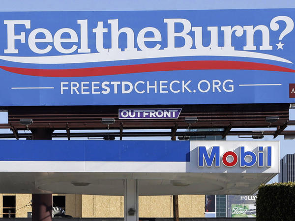 "A billboard above a gas station reads ""Feel The Burn,"" a play on 2016 presidential candidate Bernie Sanders' campaign slogan, ""Feel The Bern."" It's actually promoting tests for sexually transmitted diseases."