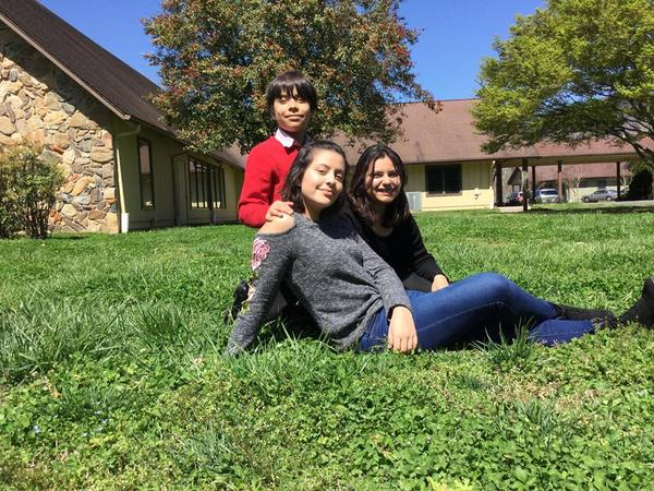 From left to right, Eddie, Natalie and Maria Fernanda Cortes, seated outside Mount Pisgah Academy, a private Seventh Day Adventist Academy near Asheville, where the two sisters will attend in Fall 2018.