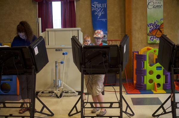 Elisabeth Ford (center), 33, holds her son, Harrison, 8 months, while casting her vote at the Trucksville United Methodist Church polling station during the 2018 Pennsylvania Primary Election  in Trucksville.