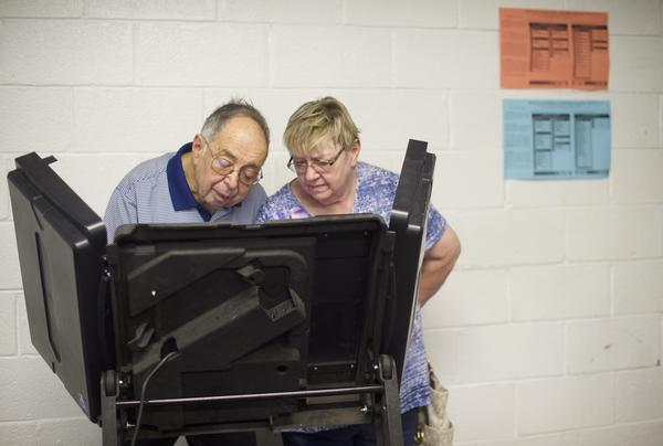 A woman assists a man vote at the Greater Nanticoke Area School District Football Stadium polling station during the 2018 Pennsylvania Primary Election in Nanticoke.