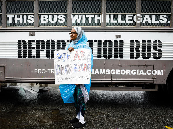 """Amina Osman protests Georgia state Sen. Michael Williams's """"Deportation Bus"""" that reads """"Fill this bus with illegals."""" She has been a resident of Clarkston, Ga. for nine years and is a refugee from Somalia."""