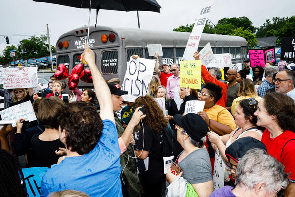 """Protesters gather outside state senator and gubernatorial candidate Michael Williams's """"Deportation Bus"""" in Clarkston, Ga."""