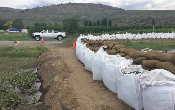 Massive sandbags protect a portion of U.S. HIghway 97 from flooding from the nearbby Okanogan River.