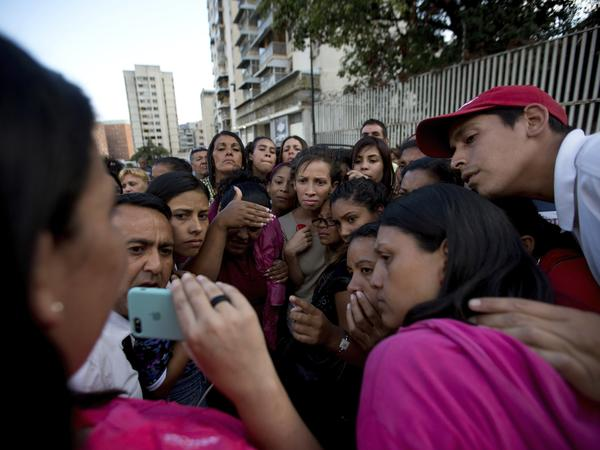 Relatives of prisoners watch in a mobile phone a video released by the prisoners outside of Venezuelan political police headquarters, SEBIN, in Caracas, Venezuela, on Wednesday.