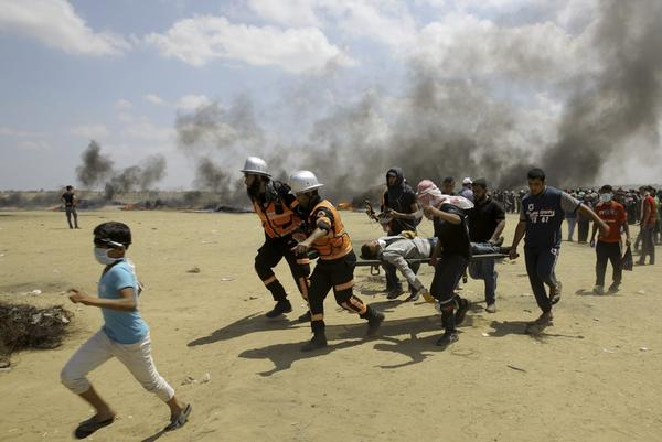 In this Monday, May 14, 2018 file photo, Palestinian medics and protesters evacuate a wounded youth during a protest at the Gaza Strip's border with Israel, east of Khan Younis, Gaza Strip. (Adel Hana/AP)