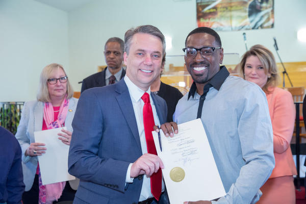 Kansas Gov. Jeff Colyer poses with Lamonte McIntyre after signing a law that provides compensation to people wrongfully convicted in Kansas. McIntyre spent 23 years in prison for a double murder he didn't commit.