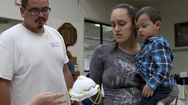 Lindsey Magnani (center), her finance Elroy Rodrigues and their children, Kahele (right) and Kayden (not shown) pick up respirators to help protect against ash from Kilauea volcano on Thursday.