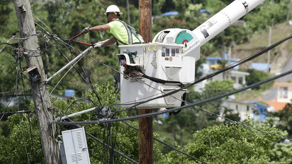 A worker from the Cobra Energy Company, contracted by the Army Corps of Engineers, installs power lines in the Barrio Martorel area of Yabucoa, a town where many residents continue without power in Puerto Rico, on May 16.