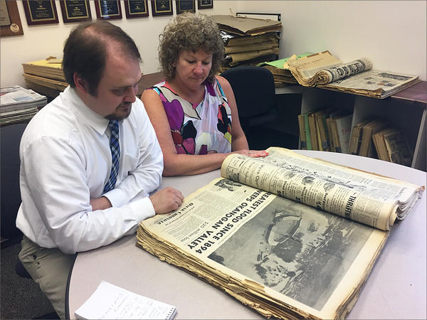 Brock Hires, managing editor of the Omak-Okanogan Chronicle, and Teresa Myers, the paper's publisher, look through photos and stories of flooding in 1972 in the newspaper's archives.