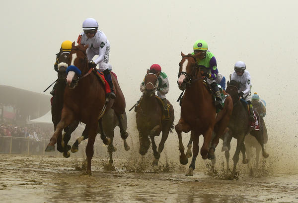 Justify, ridden by Mike Smith, wins the 143rd Preakness Stakes in the mud and fog Saturday to capture the second leg of the Triple Crown in Baltimore.