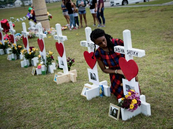 Jai Gillard, a freshman who was in the class where the mass shooting started, looks at a cross for Sabika Sheikh before signing it at a memorial for the victims of the Santa Fe High School shooting on Monday in Santa Fe, Texas.