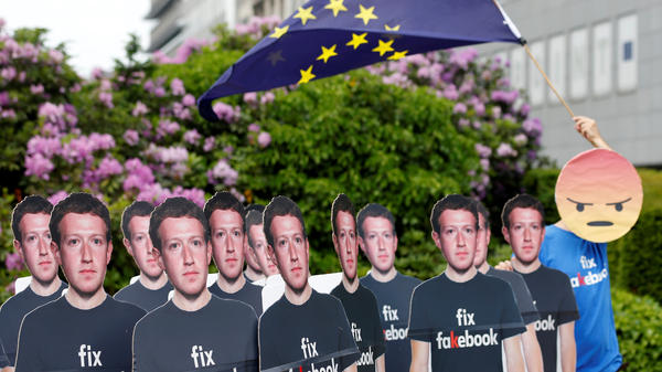A protester holds a European Union flag next to cardboard cutouts depicting Facebook CEO Mark Zuckerberg, as Zuckerberg and leaders of the European Parliament prepare to meet in Brussels.