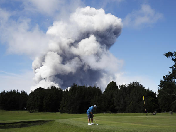 A golfer makes the best of the situation as a huge ash plume rises from Kilauea's summit nearby on Monday.