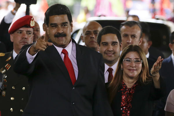 President Nicolas Maduro and his wife, Cilia Flores, acknowledge supporters at the end of a ceremony at the government-controlled National Electoral Council where he was declared winner of the presidential election, in Caracas, on Tuesday May 22, 2018.
