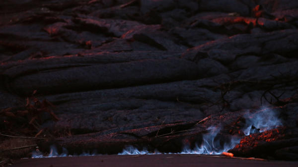 Blue flames of methane gas escape from a crack near a volcanic fissure from Kilauea in Leilani Estates, on Hawaii's Big Island, on Wednesday.
