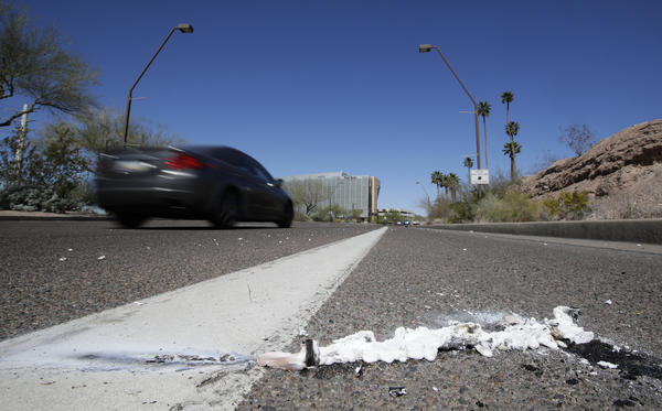 A vehicle drives by the spot where an Uber self-driving vehicle struck and killed a pedestrian earlier this year in Tempe, Ariz. The National Transportation Safety Board released a preliminary report Thursday on the collision.