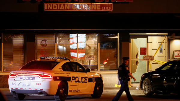 A police officer walks in front of Bombay Bhel restaurant early Friday, where two unidentified men set off a bomb Thursday night in Mississauga, Ontario.