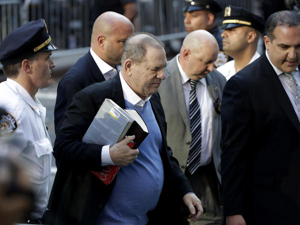 Harvey Weinstein, seen earlier Friday morning, walks into the Manhattan police station flanked by law enforcement and surrounded by members of the media.