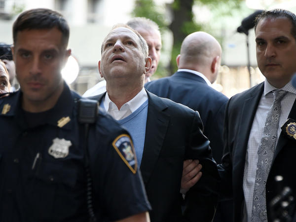 Law enforcement officers usher a handcuffed Harvey Weinstein into the courthouse for his arraignment in Manhattan on Friday.