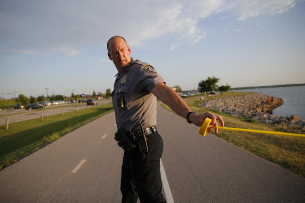 A policeman puts up crime scene tape around the scene of a shooting on the east side of Lake Hefner in Oklahoma City, Okla on Thursday. Police say an armed gunman injured three people at a restaurant before being shot dead by two armed civilians outside.