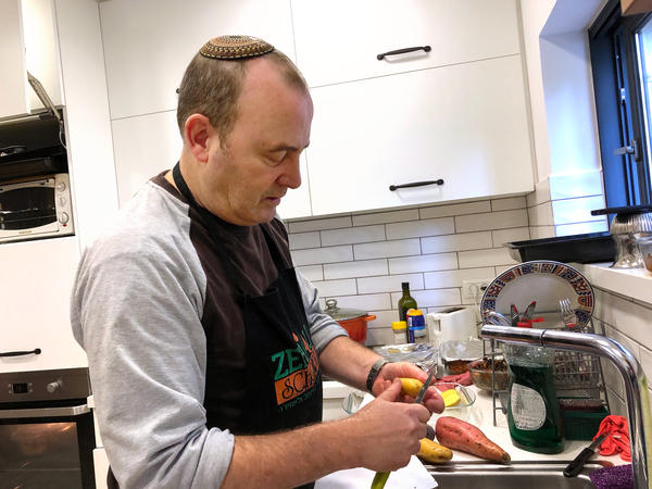 Shaike El Ami prepares Sabbath dinner in his apartment. A member of a progressive Orthodox synagogue, he tries to create common ground between Orthodox and nonreligious Jews.